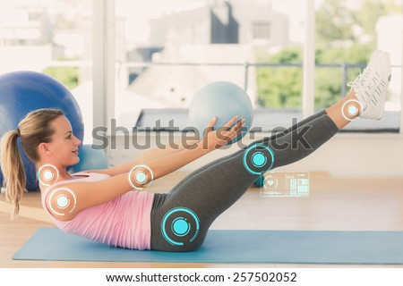 Sporty young woman stretching body in fitness studio against fitness interface - stock photo
