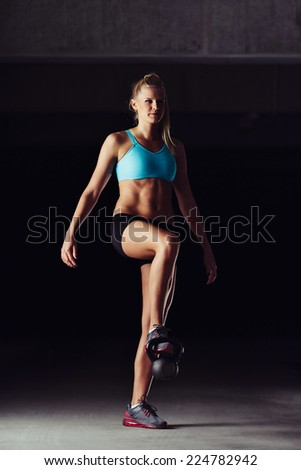 Sporty young woman toning her legs with a kettlebell - stock photo