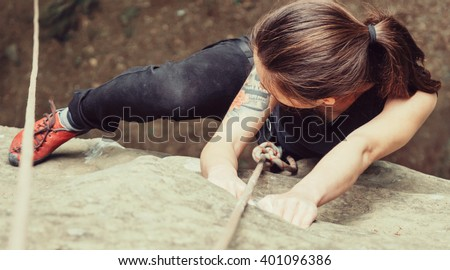 Sporty young woman wearing in safety equipment with rope climbing on stone rock in summer outdoor, top view. Close-up
