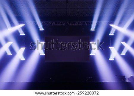 Spot lights on a Empty Stage With Blank Screen in the Middle before a Big Concert - stock photo