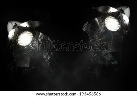 Spot studio light on black background with smoke - stock photo