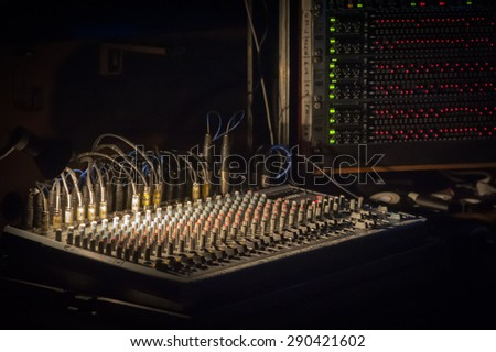 spotlight illuminating a soundboard mixer at a live music event - stock photo