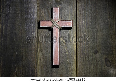 Spotlight on hanging wooden cross on old rustic wood background - stock photo
