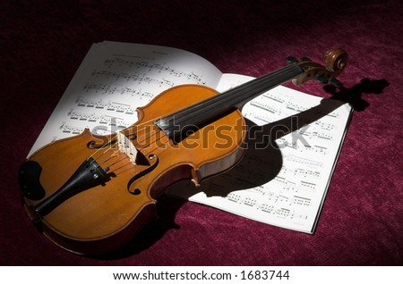 Spotlight on violin and sheet music - stock photo