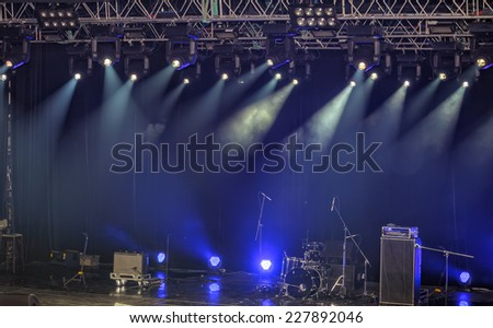 Spotlights and illumination on stage with drums, amplifiers, loudspeakers and other sound equipment