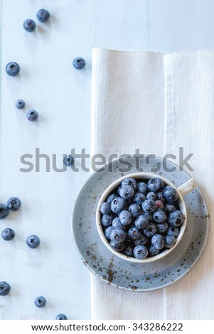 Spotted blue ceramic cup of blueberries with saucer at white textile napkin over wooden table. Rustic style. Top view. Natural day light - stock photo
