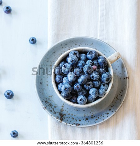 Spotted blue ceramic cup of blueberries with saucer at white textile napkin over wooden table. Rustic style. Top view. Natural day light. Square image - stock photo