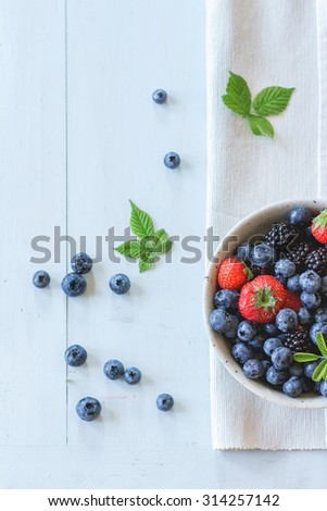 Spotted ceramic bowl with assortment berries blueberries, strawberries and blackberries at white textile napkin over wooden table. Natural day light. Top view - stock photo
