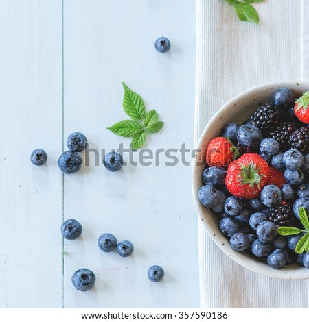 Spotted ceramic bowl with assortment berries blueberries, strawberries and blackberries at white textile napkin over wooden table. Natural day light. Top view. Square image  - stock photo