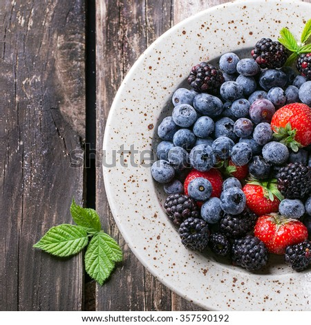 Spotted ceramic plate of assortment berries blueberries, strawberries and blackberries at old wooden table. Rustic style. Top view. Square image - stock photo