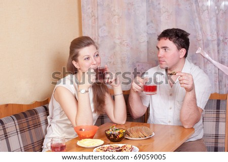 Spouses talk on kitchen behind a table - stock photo