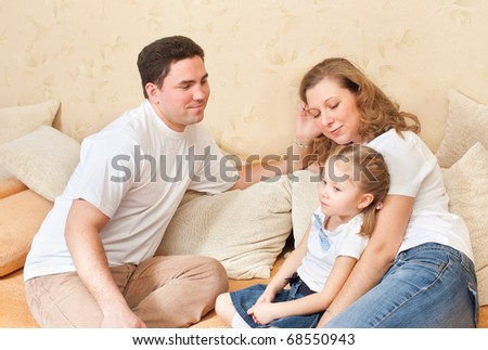 Spouses with the child sit on a sofa - stock photo