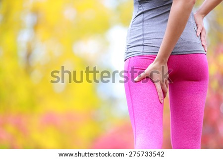 Sprain hamstring or cramps - Running sports injury with female runner. Closeup of woman back thigh. - stock photo