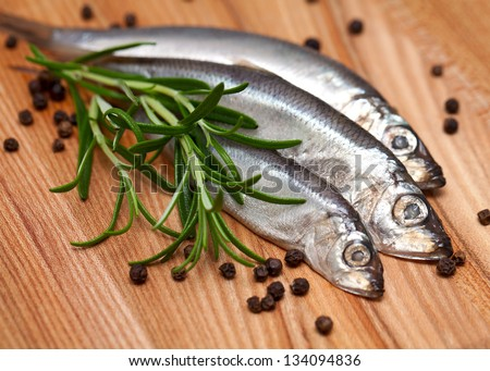 sprat fish and rosemary on wooden table - stock photo
