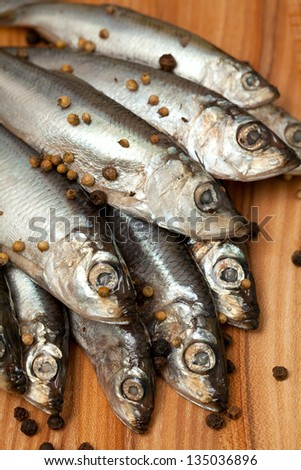 sprat fish with peppercorns on wooden board - stock photo