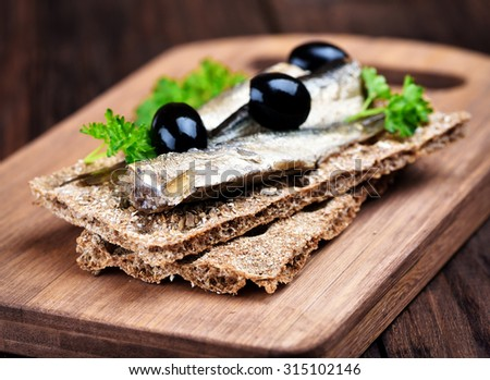 Sprats sandwich on cutting board, close up view - stock photo