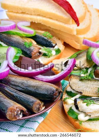 Sprats sandwiches, appetizer, bread, vegetables on paper background - stock photo