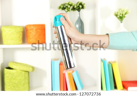 Sprayed air freshener in hand on white shelves background - stock photo