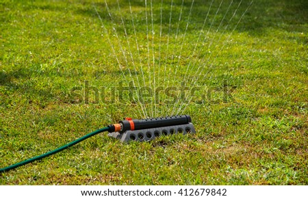 Spraying water on green lawn