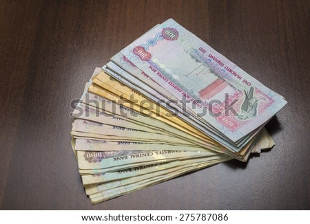 Spread of assorted currency notes of United Arab Emirates on dark background. - stock photo