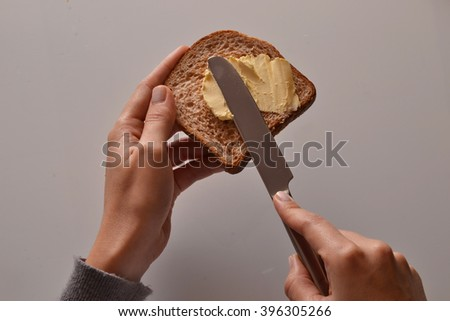Spreading butter on toast bread. - stock photo