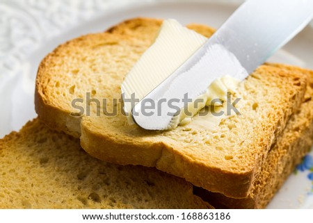 Spreading butter with a knife on sliced brown bread. - stock photo