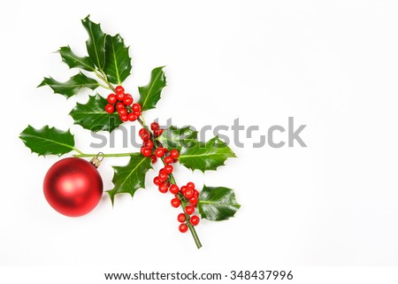 Sprig of festive  fresh Christmas holly with bright red berries and a dangling red bauble over a white background with copy space for your seasonal greeting  - stock photo