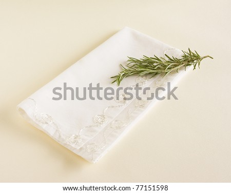 Sprig of fresh rosemary laying on top of a white napkin. - stock photo