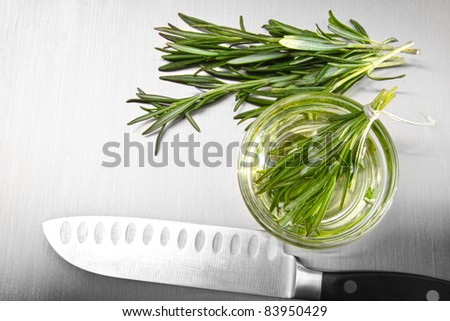 Sprigs of rosemary leaves with cutting on stainless steel counter - stock photo