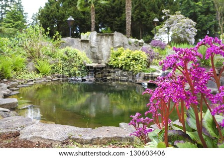 Spring American Northwest home water pond, large rock with landscape garden .