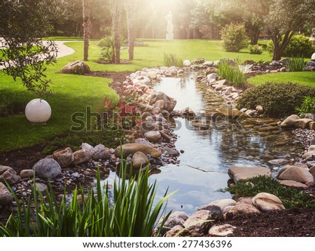 Spring and summer flowers in the Asian garden with a pond. Vintage toning  - stock photo