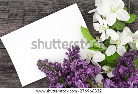 Spring apple tree blossom and lilac on rustic wooden background with empty card for greeting message. Mother's Day and spring background concept. - stock photo