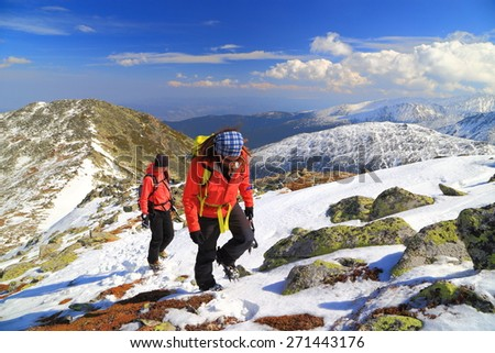 Spring ascension with mountaineers on snow covered path up to the summit - stock photo
