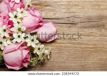 Spring background with pink roses and arabian star flower (ornithogalum arabicum) on wooden table, copy space - stock photo