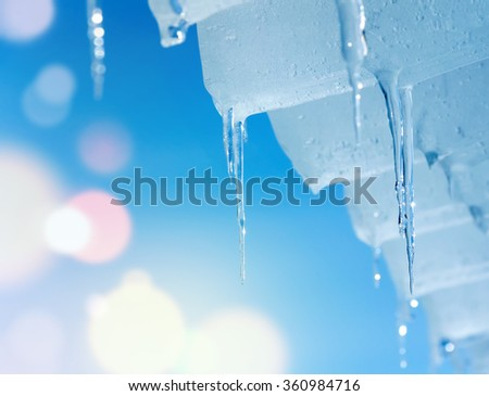 Spring background with transparent icicles against the sky - stock photo