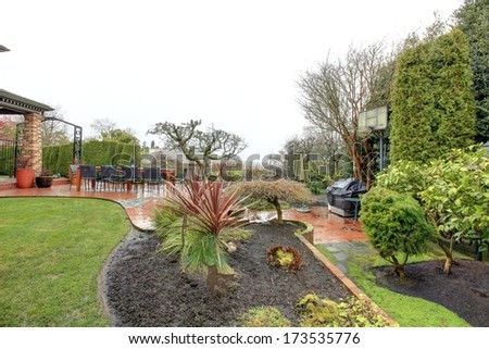 Spring backyard garden with stoned patio area after rain - stock photo