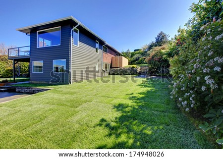 Spring beautiful backyard with green trim and flourishing bushes - stock photo