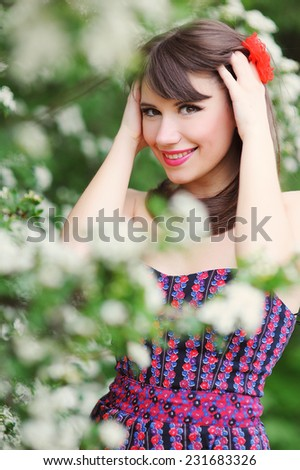Spring beauty girl with long blonde hair outdoors. Blooming trees. Romantic young woman portrait.