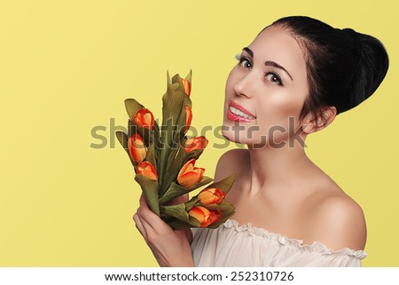 Spring beauty model studio shooting. Portrait of smiling woman brunette with flowers orange tulips on yellow background. Fashion fresh makeup.  Sensual scarlet lips. Tenderness. Romantic style. - stock photo