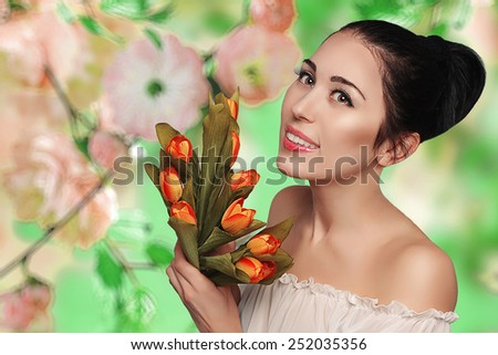 Spring beauty model studio shooting. Portrait of smiling young woman with flowers orange tulips on background blooming garden. Fashion fresh makeup.  Sensual scarlet lips.Tenderness. Romantic style. - stock photo