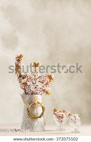 Spring blossom in jug with filled antique glasses on wooden table - stock photo