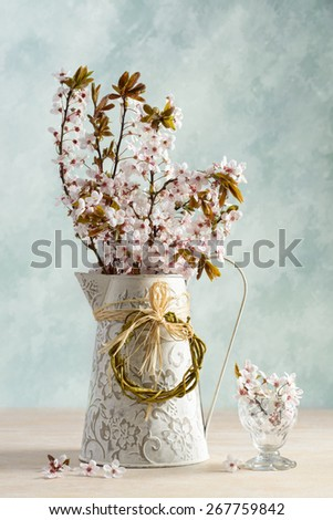 Spring cherry blossom in jug and antique glass - stock photo