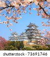 Spring cherry blossoms and the main tower of the UNESCO world heritage site: Himeji Castle, also called the white heron castle, Japan. - stock photo