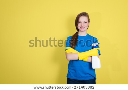 Spring cleaning. Cleaning woman with cleaning spray bottle happy and smiling. Beautiful cleaning girl isolated on yellow background with copyspace. - stock photo