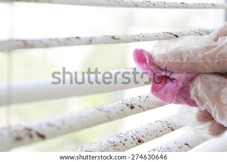 Spring cleaning, Dirty sections of white sun blinds and hand of worker who clean it up with special tool rubber protection glove window glass cleaning - stock photo