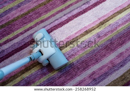 Spring cleaning - Modern living room, with a vacuum cleaner to tidy up - stock photo