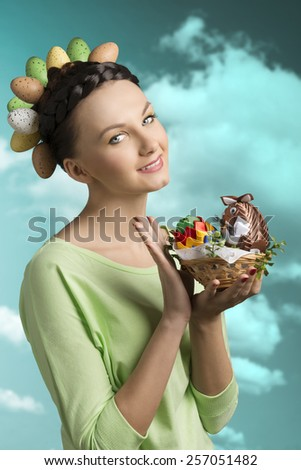 Spring, colorful, brunette woman with funny hairstyle with eggs and little basket with easter decorations.