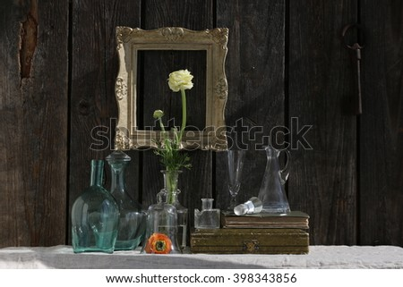 spring dark composition: flowering glass bottles, vintage group glass, wooden gold frame, old books, antique box
