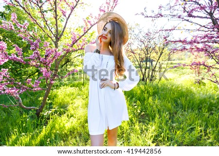 Spring fashion portrait of sensual beauty woman, long hairs pastel make up, posing at blossom garden park, sunny hot day, white vintage dress, trendy accessory, straw hat, elegant. - stock photo