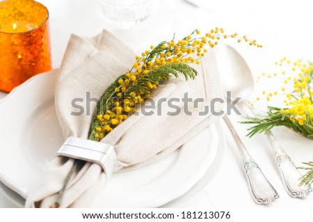 Spring festive dining table setting with yellow mimosa flowers, candles, napkins and vintage cutlery on a white wooden board. - stock photo